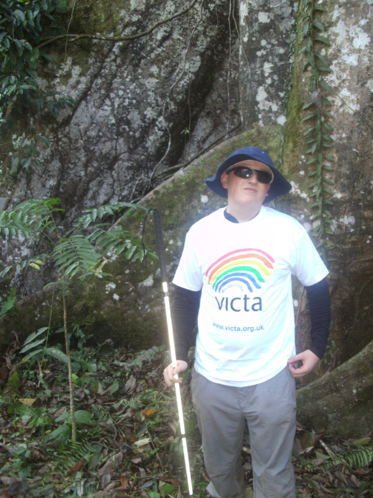 Charlie wearing his VICTA t shirt in front of a waterfall