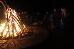 Group of young people sat around a campfire